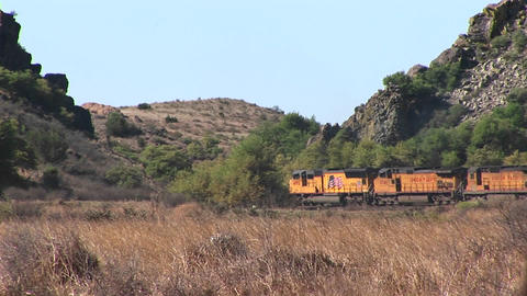 Long-shot of a train passing through a desert canyon Stock Video Footage