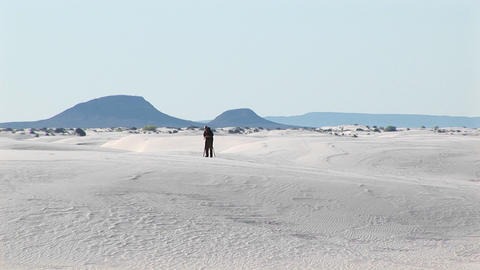 Long-shot of a photographer setting up a tripod in White Sands National Monument in New Mexico Footage
