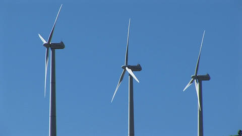 Medium-shot of three wind turbines generating power at Tehachapi, California Footage