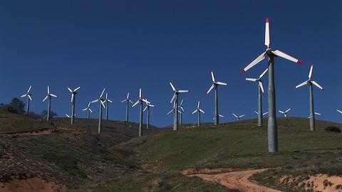 Long-shot of numerous wind turbines generating power at Tehachapi, California Footage