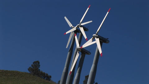 Tilt-shot of four wind turbines generating power at Tehachapi, California Footage