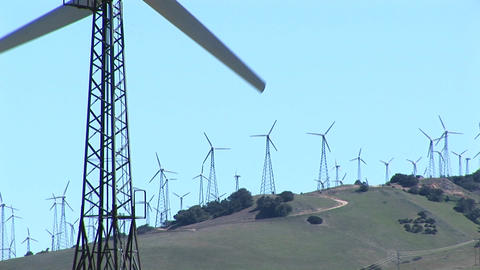 Close-up of one wind turbine with numerous turbines in the distance at Tehachapi, California Footage