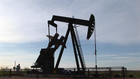 Medium shot of an oil pump turning in the New Mexico desert Stock Video Footage