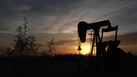 Medium shot of a silhouetted oil pump turning in the New... Stock Video Footage