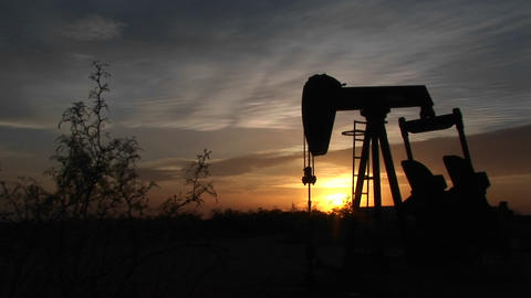 Medium shot of a silhouetted oil pump turning in the New Mexico desert Footage