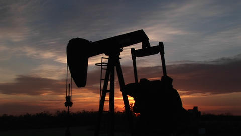 An oil rig pumps gas against a sunset Stock Video Footage