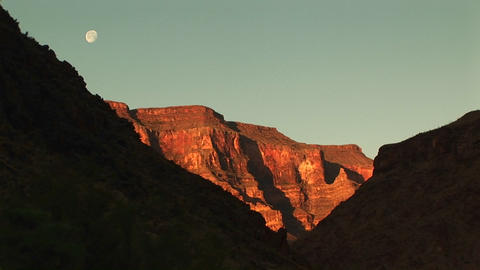 Long shot of the moon hanging over the Grand Canyon Footage