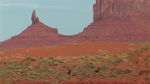 Long shot of cowboys riding through Monument Valley Tribal Park in Arizona Footage
