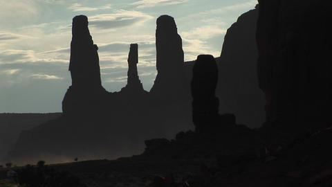 Medium shot of the silhouetted Three Sisters rock formation in Monument Valley Tribal Park, Arizona Footage