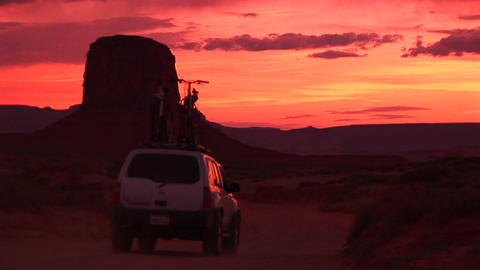 Medium shot of an SUV with bikes on top driving slowly... Stock Video Footage