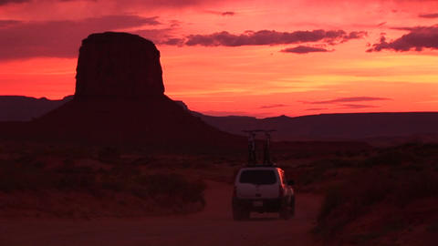 Medium shot of an SUV with bikes on top driving slowly through Monument Valley Tribal Park in Arizon Footage