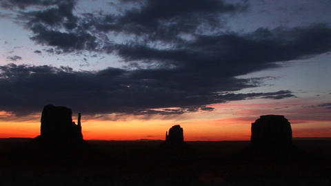 Long shot of the Mittens in Monument Valley, Arizona silhouetted at golden-hour Footage