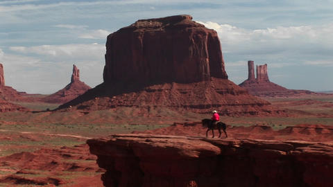 Long shot of a cowboy riding his horse to Vista Overlook in Monument Valley, Arizona Footage