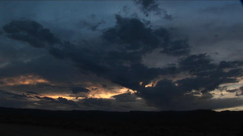 Storm clouds cluster in the sky over a desert Stock Video Footage