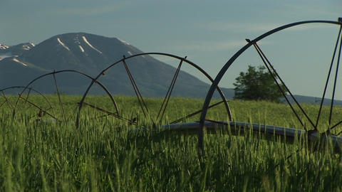 Medium shot of irrigation sprinklers on Utah farmland and the La Sal Mountains in the background Footage