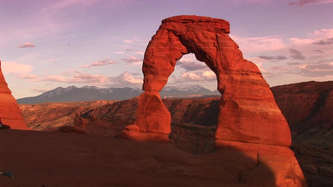 Long-shot of Delicate Arch in Arches National Park, Utah with mountains in the background Footage