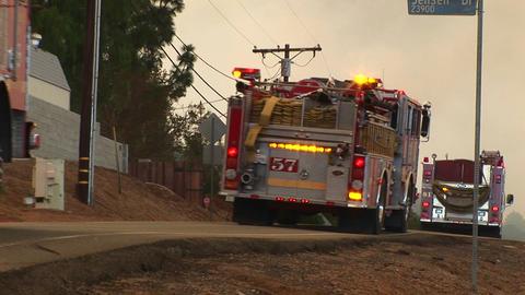 Medium shot of fire trucks racing down a street toward a wildfire Footage