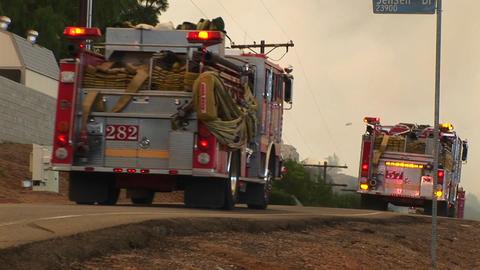 Medium shot of fire trucks racing down a street toward a... Stock Video Footage