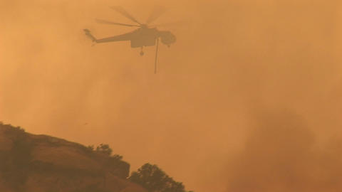 Following shot of a helicopter dropping chemicals on a wildfire in California Footage