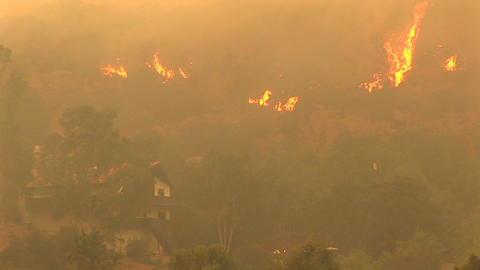 Pan-up shot of fires raging near a Southern California community Footage