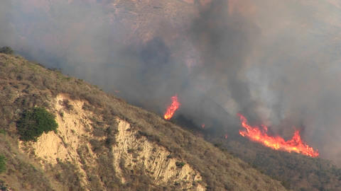 Zoom-out from wildfires burning on a smoky hillside in southern California Footage