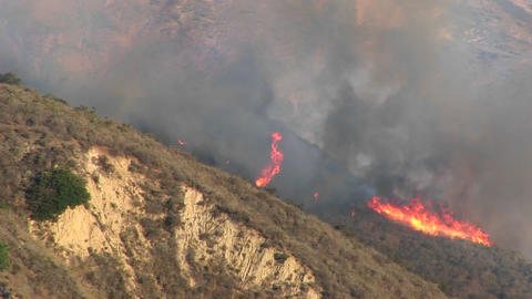 Zoom-out from wildfires burning on a smoky hillside in... Stock Video Footage
