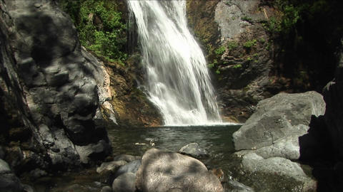 Pan-up of a waterfall flowing into a reflecting pool in... Stock Video Footage