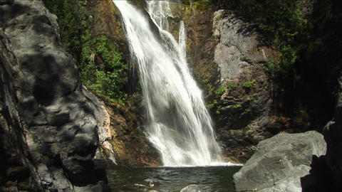 Pan-up of a waterfall flowing into a reflecting pool in Big Sur, California Footage