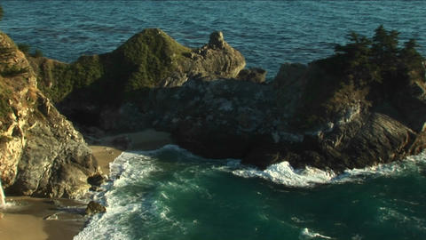 Pan-left shot of a rocky California coast and a waterfall crashing down into a secluded pool at Juli Footage