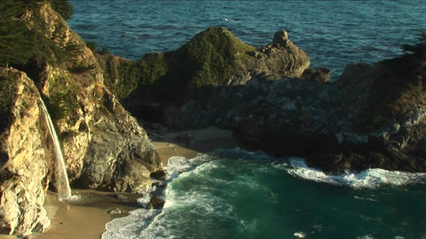 Pan-left shot of a rocky California coast and a waterfall... Stock Video Footage