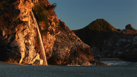 Medium-shot of a waterfall crashing down onto a secluded beach in the Julia Pfeiffer Burns State Pa Footage