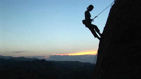 Long-shot of a rock climber silhouetted against a... Stock Video Footage