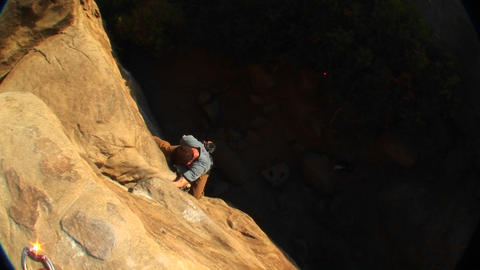 Aerial-shot of a rock climber climbing up a cliff face Stock Video Footage