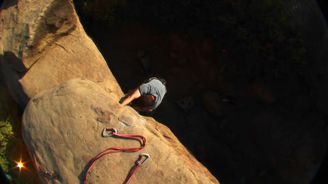 Aerial-shot of a rock climber climbing up a cliff face Footage