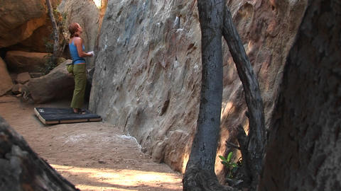 Following a woman preparing to climb a rock wall Stock Video Footage