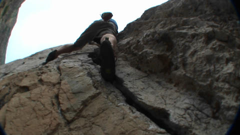 Pan-up past a rock climber scaling a cliff face Stock Video Footage