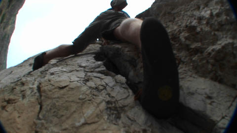 Pan-up past a rock climber scaling a cliff face Footage