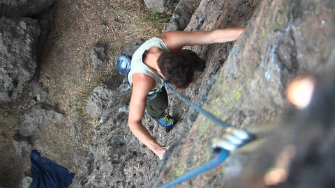 Bird's-eye shot of a rock climber scaling a cliff face Footage