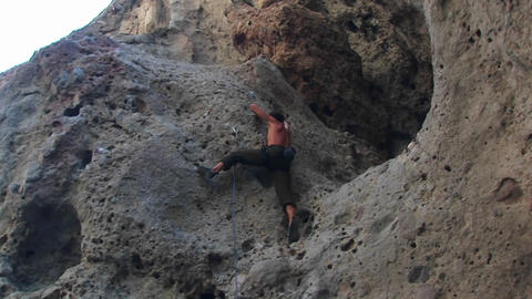 Pan-right of a rock climber scaling a cliff wall Footage