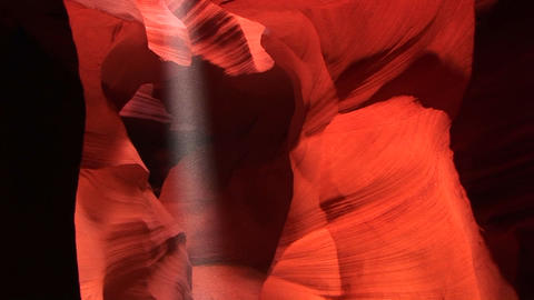 Pan-up of a shaft of light illuminating the interior of a crevasse in Antelope Canyon, Arizona Footage