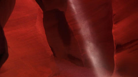 Pan-up of as a shaft of light illuminates the red rock... Stock Video Footage