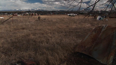 Wide shot of automobile dumpsite in Colorado with the Rocky Mountains in the background Footage