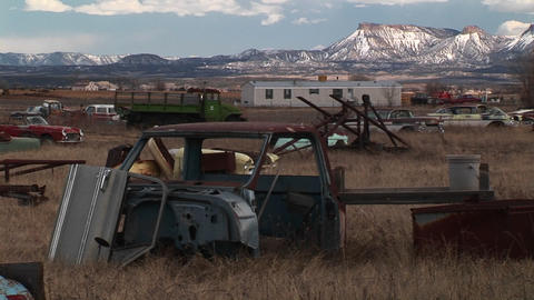 Medium shot of rusting cars in front of the Rocky Mountains Footage