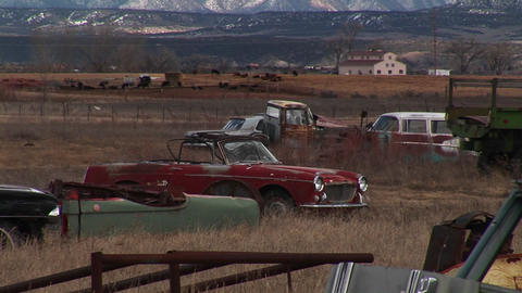 Medium shot of junked, rusting automobiles in a Colorado car graveyard littering the view of the Roc Footage