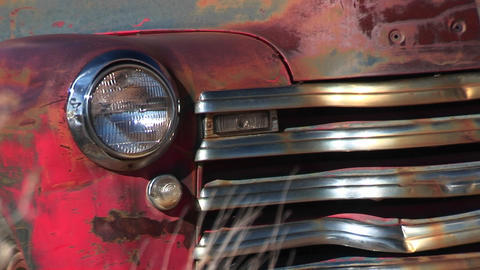 Close-up of dented and rusting abandoned pickup truck showing front passenger side headlight, grill Footage