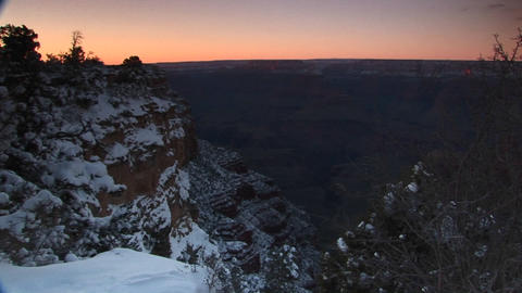 Medium wide vista of red sky behind the snowy cliffs of Grand-Canyon-National-Park Footage