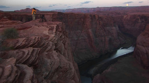 Wide shot of a photographer standing on cliff and... Stock Video Footage