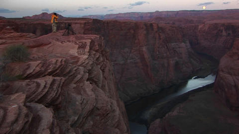 Wide shot of a photographer standing on cliff and photographing the canyons of the Colorado River as Footage