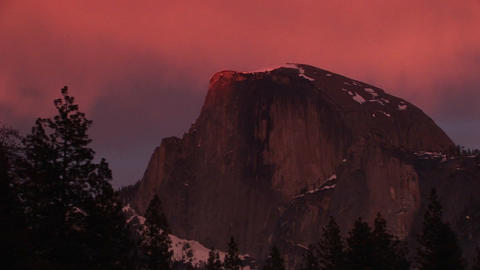 Medium wide shot of Yosemite's Half Dome in winter golden-hour Live Action