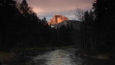 Medium wide shot of flowing Merced River framing radiant Half Dome of Yosemite-National-Park Footage